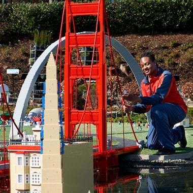 Man working on large LEGO bridge